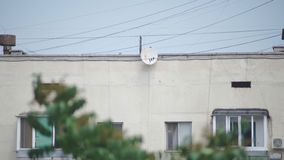 Satellite dish on the wall of a multistory building.  stock footage