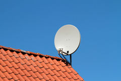 Satellite Dish. A white satellite dish on red roof Stock Images
