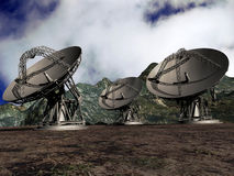Satellite dishes. Three giant satellite dishes on a field near mountains Royalty Free Stock Photo