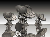Satellite dishes. Three giant satellite dishes and a domestic little one, on reflecting ground Stock Photo