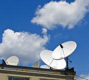 Satellite Dishes. Attached to a roof in an urban setting Stock Photos