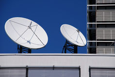 Satellite dishes. A couple of satellite dishes on the roof Royalty Free Stock Photography