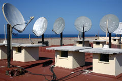 Satellite Dishes. Group of satellite antennas on a root top Royalty Free Stock Image
