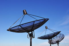 Satellite dishes. Group of satellite dishes on blue sky background Royalty Free Stock Photo