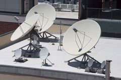 Satellite Dishes. Point skyward on top of a building stock photo
