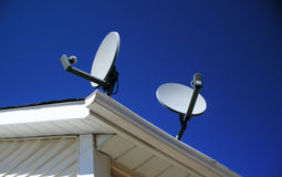 Satellite Dishes atop a Home. These satellite television receiving dishes atop a home are pointed at two different satellites Royalty Free Stock Photo