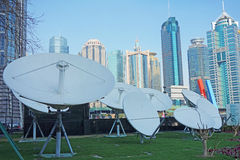 Satellite dishes with modern buildings Royalty Free Stock Photo