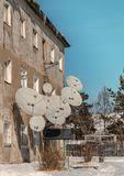 Satellite dishes in an old three-story house. Several satellite dishes of different sizes, located on the wall of an old three-story building Stock Photo