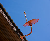 Satellite dishes. Orange satellite dish attached to the roof stock images