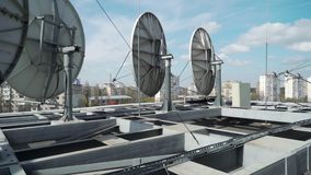 Satellite dishes on the roof of the building.  stock footage