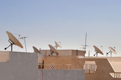 Satellite dishes on rooftop in Tunisia. Pointing in the same direction with a blue sky in the background Stock Image