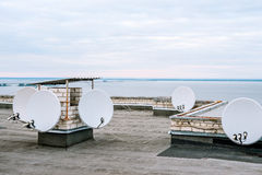 Satellite dishes, satellite antennas on top of the building in urban area near the river Stock Image