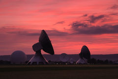 Satellite dishes at sunset. Scenic view of modern satellite dishes or early warning radar silhouetted with red sunset and cloudscape background Royalty Free Stock Photo