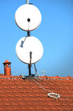 Satellite dishes on a tiled roof Royalty Free Stock Photos