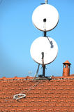 Satellite dishes on a tiled roof Stock Photography