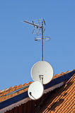 Satellite dishes on a tiled roof Royalty Free Stock Images