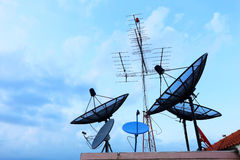 Satellite Dishes and TV antennas on the house roof Royalty Free Stock Images