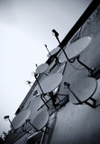Satellite dishes wall. Outside of a house covered with many satellite dishes. Blue toned photo Stock Photos