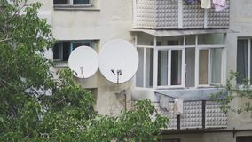 Satellite dishes on the wall of a multistory building.  stock video footage