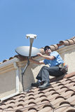 Satellite Installer on Roof 2. Installation of satellite dish TV system in sitting position Stock Photos