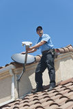 Satellite Installer on Roof. Installation of satellite dish TV system on Spanish tiled roof Royalty Free Stock Images