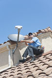 Satellite Installer on Roof. Installation of satellite dish TV system on Spanish tiled roof Royalty Free Stock Photos