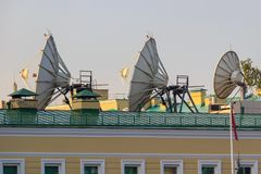 Satellite parabolic antennas on building roof closeup in sunny morning stock image