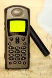 Satellite phone. Dark satellite phone on the map of desert Royalty Free Stock Images