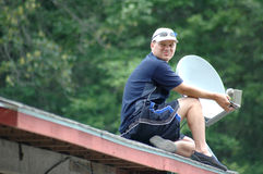 Satellite TV. Man on roof installing a satellite for TV sports Royalty Free Stock Photography