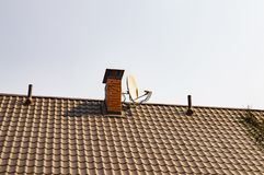 Satellite TV antenna near the chimney pipe on the roof of the house royalty free stock image