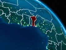 Satellite view of Benin at night. Satellite view of Benin highlighted in red on planet Earth at night with borderlines and city lights. 3D illustration Royalty Free Stock Images