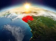 Gabon from space in sunrise. Satellite view of Gabon highlighted in red on planet Earth with clouds during sunrise. 3D illustration. Elements of this image Royalty Free Stock Images