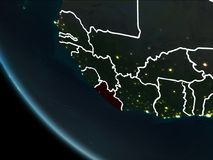 Satellite view of Liberia at night. Satellite view of Liberia highlighted in red on planet Earth at night with borderlines and city lights. 3D illustration Royalty Free Stock Images