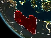 Satellite view of Libya at night. Satellite view of Libya highlighted in red on planet Earth at night with borderlines and city lights. 3D illustration. Elements Stock Photos