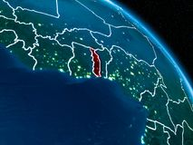 Satellite view of Togo at night. Satellite view of Togo highlighted in red on planet Earth at night with borderlines and city lights. 3D illustration Stock Images