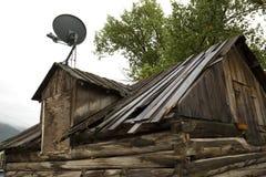 Satellitenschüssel auf altem Blockhaus im Verfall, Jackson, Wyoming Lizenzfreies Stockbild