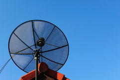 Satellitenschüssel auf dem Dach auf Hintergrund des blauen Himmels Lizenzfreies Stockfoto