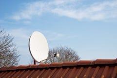 Satellitenschüssel auf dem roten Dach Stockfoto