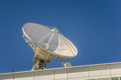 Satellitenschüssel gegen blauen Himmel Stockfotos