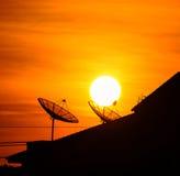 Satellitenschüssel im Himmelsonnenuntergang Stockfotos