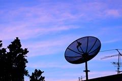 Satellitenschüssel im twilight Himmel lizenzfreies stockfoto
