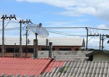Satellitenschüssel und Fernsehantennen auf dem Hausdach Stockfotos