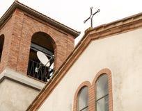 Satellitenschüssel und Kreuz auf Kirche Stockfotografie