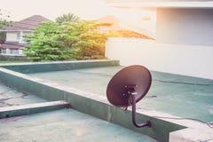 Satellitenschüsselantenne auf das Gebäude und die Sonne Lizenzfreie Stockbilder