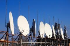 Satellitenschüsseln auf dem Dach Stockbilder