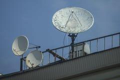 Satellitenschüsseln auf dem Dach gegen den blauen Himmel stockbilder