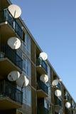 Satellitenschüsseln auf einer Wohnanlage Stockfotografie