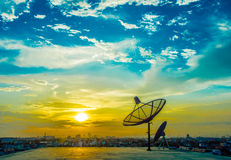 Satellitenschüsseln mit Sonnenuntergang Stockfotos