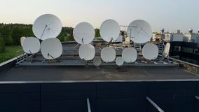Satellites dishes transmitting and receiving digital television broadcast signals. Aerial drone footage. Communication antennas and towers. Satellite dishes on stock video