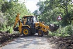 Sathyamangalam, tamil nadu India, Czerwiec, - 24, 2015: Ekskawator robi roadwork po środku Sathyamangalam lasu Zdjęcie Stock